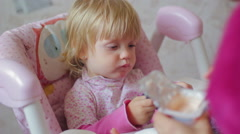 Small child eats food from a spoon Stock Footage