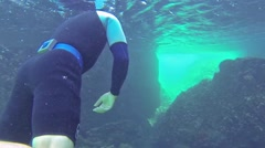 Free diving through a coral reef at Bartolome Island in Galapagos National Park, - stock footage