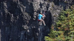 Stock Video Footage of Rock climber rappeling down