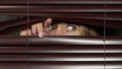 Nervous young woman peers anxiously through blinds Stock Footage