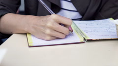 Female hands writing notes in in notebook on the table Stock Footage