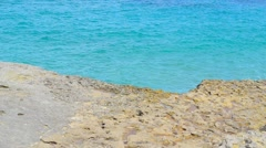 Turquoise water and yellow rock Stock Footage