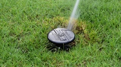 Sprinkler on grass field Stock Footage