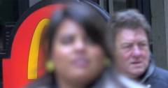 People passing by McDonald's sign in the city Stock Footage