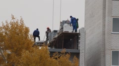 A team of masons building brick multistory house in autumn Stock Footage