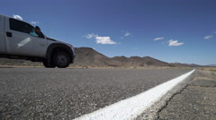 Vehicle Travels Along A Road in the Desert Stock Footage
