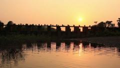 Two kids crossing the bridge during sun set in Indian village - stock footage