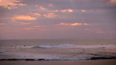 Stock Video Footage of Wide shot of large group of surfers surfing at sunset