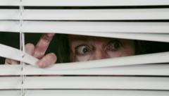 Elderly woman peeps through her blinds, gets a shock or a fright. - stock footage