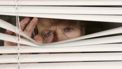 Elderly woman peers suspiciously through blinds, looking from side to side. Stock Footage