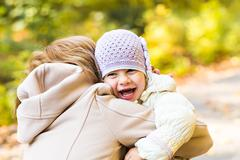 Happy family: mother and child little daughter play cuddling on autumn walk in Stock Photos