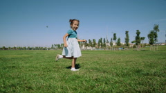 Slow motion clip of 4-year old Asian girl running in field Stock Footage