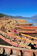 Lugu Lake, China – Dec 30 2013: Local Boat owner cleaning their boat. Stock Photos