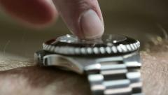 Man's finger impatiently taps his generic diver-style wristwatch. Stock Footage
