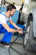 Auto mechanic changing tyre on car - stock photo