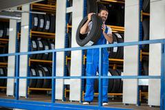 Auto mechanic carrying tire - stock photo