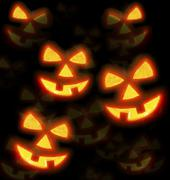 Stock Photo of Lots of pumpkins lit brightly against a black