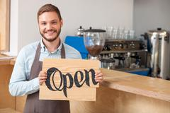 Attractive young worker is inviting in coffee shop - stock photo