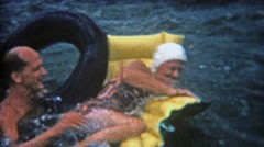 1956: Man trying to flip women from raft while floating in lake waters. - stock footage