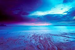 Colorful cloudy sunset on beach Stock Photos