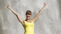 Young woman raising her arms in front of the waterfall - stock footage