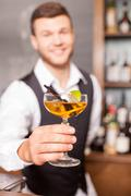 Handsome young barman is working in bar Kuvituskuvat