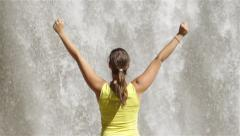 SLOW MOTION CLOSE UP: Young woman looking at waterfall and celebrating - stock footage