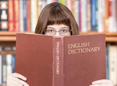 Girl looks over English Dictionary and books Stock Photos