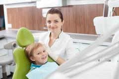 Cheerful female dentist is working with small child Stock Photos