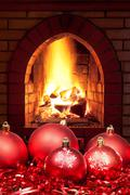 Red Xmas baubles and tinsel with home fireplace Stock Photos