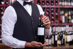 Professional young sommelier is working in liquor store - stock photo