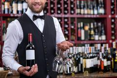 Cheerful young waiter is carrying alcohol drink in cellar - stock photo