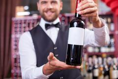 Handsome young male sommelier in liquor store - stock photo