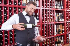 Stock Photo of Attractive young waiter is working in liquor store