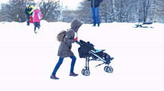 Woman Carries a Stroller with Baby Up to the Hill in Winter - stock footage
