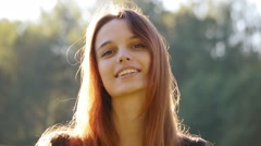 Pretty happy girl smiling into the camera, sunny day, close up, slow motion. Stock Footage