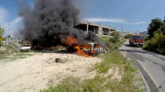 Two cars explode and burn after rocket attack - stock photo