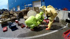 Firefighters with protective gear seal leak of hazardous materials - stock photo
