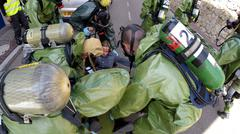 Soldier with gas mask help injured person after leak of hazardous material Stock Photos