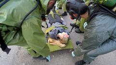 Soldier with gas mask help injured person after leak of hazardous material - stock photo