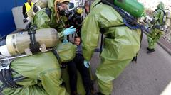 Stock Photo of Soldier with gas mask help injured person after leak of hazardous material