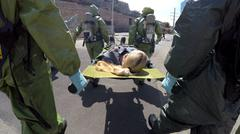 Soldiers carry an injured person on stretcher after leak of toxic materials - stock photo