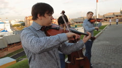Street Musicians. Guys Playing Musical Stringed Instruments On The Street - stock footage