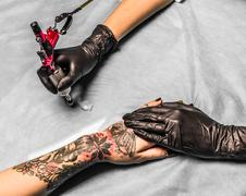 Tattoo master take paint in salon - stock photo