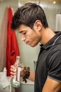 Handsome young man using mouthwash, in bathroom - stock photo