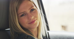Beautiful woman sitting in car smiling at camera Stock Footage