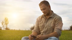 Young man with Smartphone in nature - stock footage