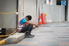 Exhausted Construction Worker Takes a Break in Singapore Kuvituskuvat