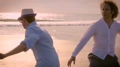 Hand held slow mo of two men having fun together at the beach pretending to surf - stock footage