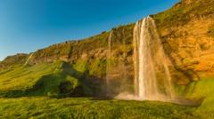 Seljalandsfoss waterfall with rainbow during sunset Stock Footage